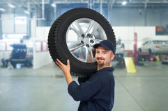 Car mechanic with a tire . Stock Photos