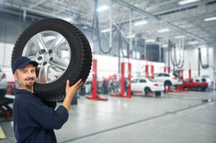 Car mechanic with a tire . Stock Images