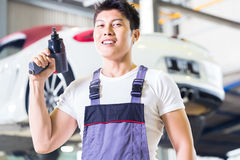 Car mechanic with tool in Asian Chinese auto workshop. Asian Chinese car mechanic with tool in front of luxury car in auto workshop stock image