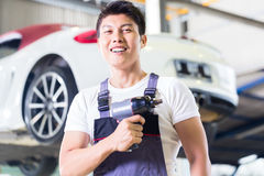 Car mechanic with tool in Asian Chinese auto workshop. Asian Chinese car mechanic with tool in front of luxury car in auto workshop royalty free stock image