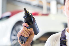 Car mechanic with tool in auto workshop with tool. Car mechanic with tool in front of luxury car in auto workshop royalty free stock photo