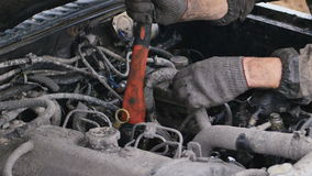 Car mechanic try to do fast repair of car with axe outdoors. All is dirty. stock video