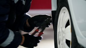 Car mechanic unscrewing pin car wheel of automobile in service. Telephoto stock video footage