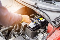 Car mechanic use voltmeter to check car battery voltage level. For background stock images