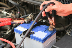 Car mechanic uses battery jumper cables charge a dead battery. Stock Photos