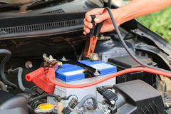 Car mechanic uses battery jumper cables charge a dead battery. Stock Image