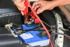 Car mechanic uses battery jumper cables charge a dead battery. Stock Photo