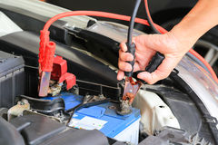 Car mechanic uses battery jumper cables charge a dead battery. Stock Images