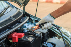 Car mechanic uses battery jumper cables to charge a dead batte Stock Image