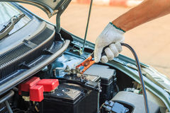 Car mechanic uses battery jumper cables to charge a dead batte Royalty Free Stock Photos