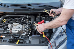 Car mechanic using car battery jumper cable Royalty Free Stock Photos