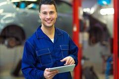 Car mechanic using a digital tablet. In an auto repair shop Royalty Free Stock Photos