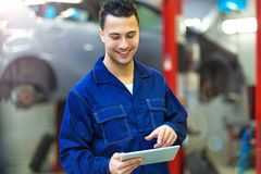 Car mechanic using a digital tablet. In an auto repair shop Stock Images