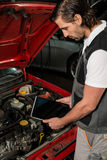 Car mechanic using digital tablet. Close-up of a car mechanic using digital tablet in a garage, the tablet displaying a blank screen that can easily be replaced Royalty Free Stock Photography