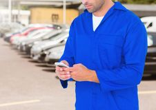 Car mechanic using mobile phone against car parked Stock Photo
