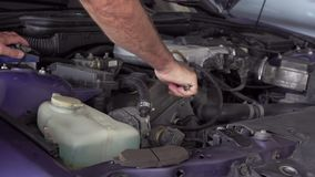 Car mechanic using a screw wrench to tighten the screws of an engine part.  stock video