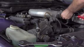 Car mechanic using a screwdriver to tighten the screws of an engine part.  stock video footage