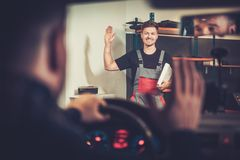 Car mechanic welcomes new client to his auto repair service. Royalty Free Stock Photography