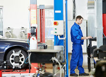 Car mechanic at wheel alignment with computer. Car mechanic working with computer during suspension adjustment and automobile wheel alignment work at repair stock image