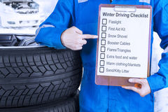 Car mechanic with winter driving tips. Close up of a car mechanic leaning on a pile of tires and showing a winter driving tips on the clipboard Stock Image