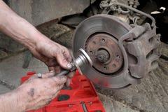 Car mechanic work on disc brakes. Mechanic fix car disc brakes with disc brake caliper tool set Royalty Free Stock Images