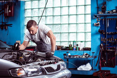 Car mechanic at work. Young strong car mechanic at work in shop Stock Image