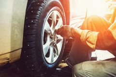 Car mechanic worker doing tire or wheel replacement in garage of repair service station. Sunlight effect, toned Royalty Free Stock Images