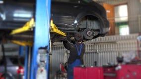 Car mechanic worker repair suspension of lifted automobile at repair garage. stock video