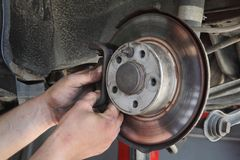 Car mechanic working on disc brakes. Mechanic servicing disc brakes of car, closeup of workers hands Royalty Free Stock Images