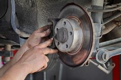 Car mechanic working on disc brakes. Mechanic servicing disc brakes of car Stock Photos