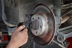 Car mechanic working on disc brakes. Mechanic servicing disc brakes of car at modern vehicle, closeup of hand Stock Photo