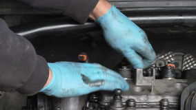 Car mechanic working under hood or bonnet. Car mechanic working under bonnet or hood hands close up stock footage