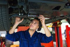 Car mechanic working on the underside of a car Royalty Free Stock Photos