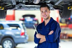 Car mechanic working on the underside of a car Stock Photography