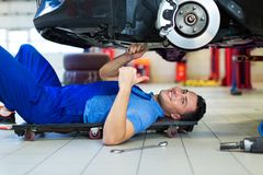 Car mechanic working on the underside of a car Stock Photos