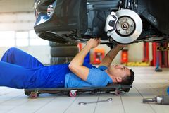 Car mechanic working on the underside of a car Royalty Free Stock Photography