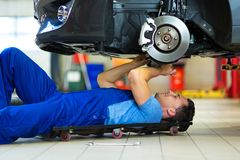 Car mechanic working on the underside of a car Stock Image