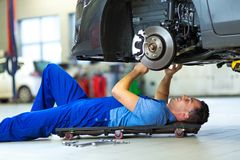 Car mechanic working on the underside of a car Stock Photo