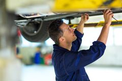 Car mechanic working on the underside of a car Royalty Free Stock Images