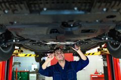 Car mechanic working on the underside of a car Royalty Free Stock Image