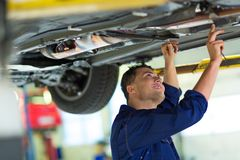 Car mechanic working on the underside of a car Royalty Free Stock Photo