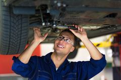 Car mechanic working on the underside of a car. Car mechanic working on the undere of a car, smiling royalty free stock photos