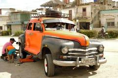 Car mechanic working on a wheel change of classic vehicle Stock Image