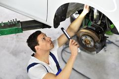 Car mechanic works in a workshop, repair of cars. And breaks Royalty Free Stock Photography