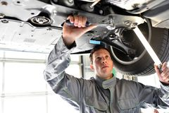 Car mechanic in a workshop - engine repair and diagnosis on a ve. Hicle Royalty Free Stock Images