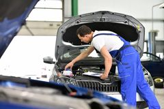 Car mechanic in a workshop - engine repair and diagnosis on a ve. Hicle stock photography