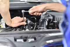 Car mechanic in a workshop repairing a vehicle. Closeup detail tool stock photo