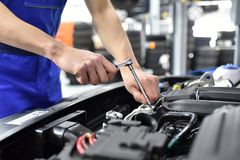 Car mechanic in a workshop repairing a vehicle. Closeup detail with tool stock images