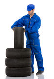 Car mechanic. Young car mechanic changing car tires on white background Stock Photography