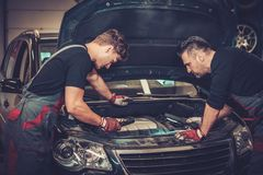 Car mechanics checking under hood in auto repair service. Royalty Free Stock Photos